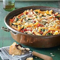 Ingredients: 12 ounces casarecce or fusilli pasta,  1 (28-oz.) can diced tomatoes,  2 cups chicken broth,  1/2 medium-size yellow onion, sliced,  4 garlic cloves, sliced,  1 teaspoon dried oregano,  1/3 cup firmly packed fresh basil leaves,  2 teaspoons kosher salt,  1 tablespoon olive oil,  1/4 teaspoon dried crushed red pepper (optional)  1 (6-oz.) package baby spinach,  Freshly grated Parmesan cheese.