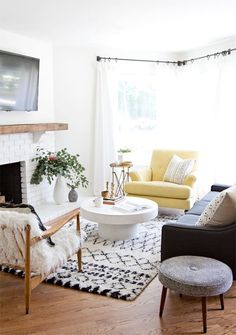 Modern bohemian-meets-midcentury living room with a Moroccan rug, sheepskin arm chair and yellow accent chair.