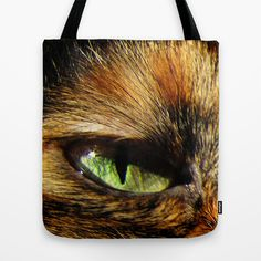 Cat Eyes Tote Bag A stunning tote bag for the cat lover with an image of a cat's green eyes with tiny star shaped sparkles are staring out at you.