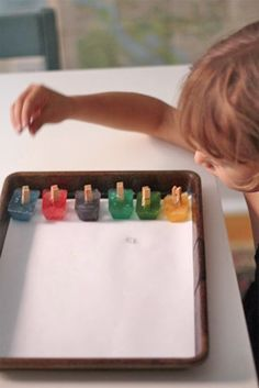 Ice painting - make colored ice cubes with liquid food coloring and clothes pins for handles.  Fun process art!