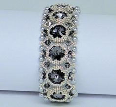 This rich and sparkling bracelet was made with 10,12mm black diamond rivoli swarovski crystals,3mm,4mm black diamond swarovski crystal bicones,4mm silver swarovski crystal pearls and seed beads.Simple,jet very Elegant this bracelet just sparkles with the colors silver and Black Diamond AB and