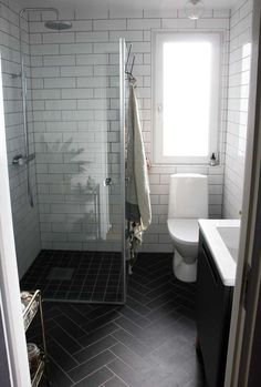 I love everything about this bathroom! The black herringbone floor, the white su… I love everything about this bathroom! The black herringbone floor, the white subway tiles with black grout and the frameless shower doors. Bad Inspiration, Bathroom Inspiration, Planchers En Chevrons, Frameless Shower Doors, Bathroom Design Small, Small Bathrooms, Narrow Bathroom, Bathroom Mirrors, Tiled Bathrooms
