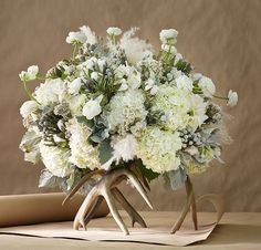 Arrangement contains hydrangea, ranunculus, dusty miller, brunia, cotton bolls, acorns, cymbidiums, pampas grass plumes, and rice flower.