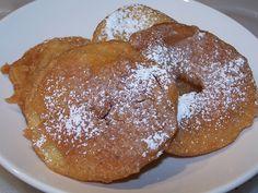 Apple Fritters  - 4 apples, 2 tsp lemon juice, 2 c complete pancake mix, 1½ c water, ½ tsp ground nutmeg, ½ c confectioner's sugar, veg oil