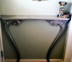 Re-purposed Antique Mirror Frame.  Give an old frame new life by using parts of it as legs for an entryway table.
