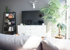 Dream setup. White credenza-buffet as media stand, huge TV on top, grey-beige L-shaped couch, a small industrial bookcase and a big plant near the windows.  Maybe add a sound bar and some extra media equipment and you're set.