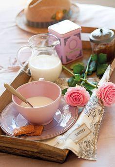 Detalle de bandeja de desayuno sobre la cama con bol rosa, jarra de cristal y rosa
