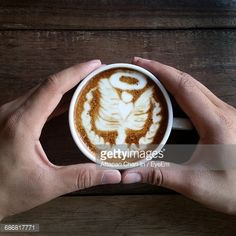 Stock Photo : Directly Above View Of Hands Holding Cappuccino Cup With Froth Art