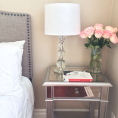 Guest bedroom - grey headboard with stud detail edging, white tufted comforter set, glass lamp, mirrored nightstand and pink roses - Stylish Petite