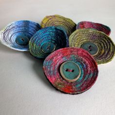 This brooch has been created from a piece of handmade felt made using traditional methods from wool and silk. I have stitched into the felt to create structure and pattern, and to give the brooch a 3-dimensional appearance.    Stitched into the middle is a gorgeous ceramic button handmade by Jude Allman.    The brooch measures approximately 6.5cm/2.25inches in diameter.    Free P&P when purchased with another item from my shop.