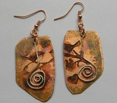 Stamped a design on a sheet of copper, then cut some shapes free-hand. Use paint dabbers and alcohol inks for a little color, and created an artistic wire spiral. They are close to 2.5 inches long. Beadlady3 aka Cindy