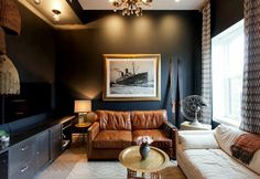 Living room with black walls, a cream sofa, and a burnt British tan leather loveseat – designer Genevieve Gorder's home