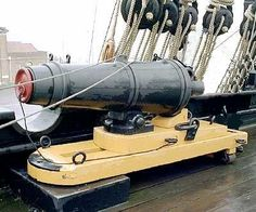 Carronade (short cannon) mounted on a slide. Carronades had a much shorter range than long guns, but were lighter than long guns of the same caliber, so they could be mounted on a higher deck or a smaller ship.