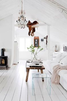 Modern elements scattered throughout, extend a dynamic feature to the rustic aesthetic of the whitewashed room.