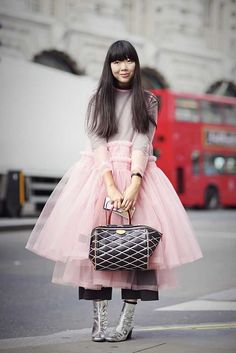 Susie Lau wears a pink tutu style dress with metallic silver ankle boots and a Louis Vuitton handbag - London Fashion Week