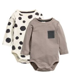 BABY EXCLUSIVE/CONSCIOUS. Long-sleeved bodysuits in organic cotton jersey with snap fasteners on one shoulder and at gusset. One bodysuit with printed pattern, one with chest pocket.