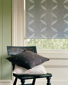 Vines traced from an Early American stencil wind down a pale-gray roller shade in four columns that mirror one another.