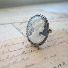 A beautiful and feminine portrait cameo has been set in a silver plated bezel ring setting to create this vintage inspired ring. The cameo measure 18x13mm and the ring is adjustable to fit most sizes.All Out of the Blue jewelry includes free gift wrap.