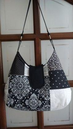 Bolsa em tecido 100% algodão (parte externa e interna) e estruturada com manta R1. Possui bolsos internos com fechamento em botão ímantado e alças com argolas de metal. Cores estampadas em preto, branco e cinza. Peça única.