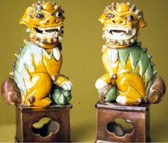 Pair of sancai glazed porcelain Foo dogs. Male with ball under paw; female with puppy under paw.