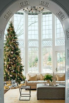 The decorated arch leading into room with double high ceiling, wall of windows bisected with diamond- paned panels. Fabulous