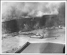 Photograph of hangar and planes damaged and set afire by Japanese bombs at Pearl Harbor. (12/07/1941)