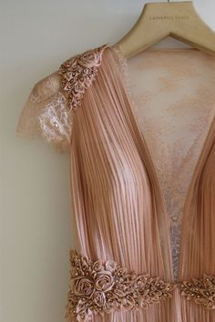 Beautiful lace and 3D florals on this pleated nude-pink dress.