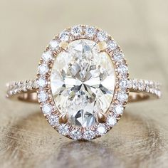 A halo setting and diamond accents along the side complement this oval-cut ring by Ken and Dana Designs.