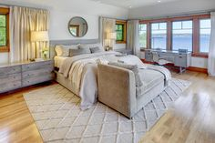 Upstairs in this Craftsman-style home is a beautiful and serene master bedroom suite with gorgeous views of the lake. The homeowner wanted a contemporary style, so a soft gray palette is paired with clean-lined yet comfortable furnishings.