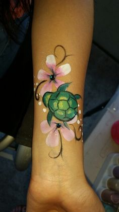 Cute turtle and pink Hawaiian flowers face and body paint by Sarah Pearce at Earth Fairy Entertainment in Portland Oregon