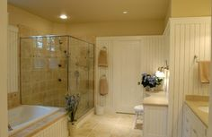 neutral, calm bathroom in cream and white.  beadboard paneling, glass shower enclosure.