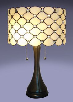 Fancy this modern take on a chic Tiffany-style lamp design. Your decor will love the creamy stained-glass lampshade and the sassy bottom scalloped edge. The crafted bronze base is beautiful. The 22-inch height fits on any accent or end table.