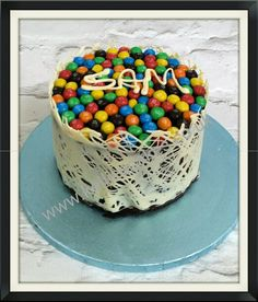 Made this cake for my son's birthday today.  Three layers of chocolate sponge,  filled and iced with chocolate ganache, white chocolate side decoration, and topped with m and m's. Yum!