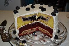 """A """"piecaken"""" -- the pastry version of the savory """"turducken."""" It's pretty overwhelming...I'm guessing it's  blue/blackberry and apple pies baked within a layer of lemon/yellow and red velvet cakes in white frosting..."""