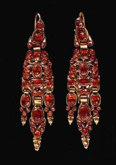Earrings, late 17th century. The elongated drop, like the bow, became popular in peninsular women's fashion during the second half of the 17th century. The earrings shown here are composed of five trimmed and pierced gold plates linked by thin connecting plates. Garnets, of various sizes, are arranged between the plant motifs.