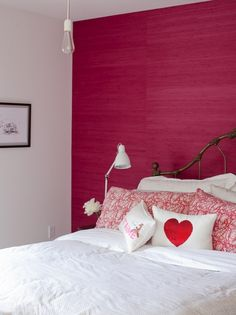 The Cross Decor & Design | Hot pink grasscloth wallpaper | Vintage style brass bed | White bed linens | Hot pink and white paisley pillows | Sequined heart pillow | Embroidered 'Je t'aime' pillow