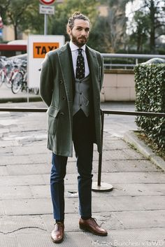 Long olive coat, tapered and cuffed navy trousers, textural waistcoat, dress shirt, tie, rich brown oxfords
