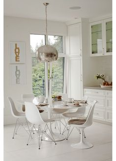 Chic eat-in kitchen features hammered metal pendant over Oval Saarinen Dining