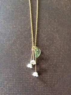 Pretty, exquisite, dainty and nicely detailed Lily of the Valley necklace. Pendant is 1 3/8 L X 1/2 W and is on an 18 gold tone chain. Similar bell flower necklace in white, pale pink and pale yellow available under the following listing: