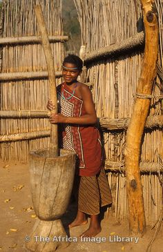 Photos and pictures of: Swazi girl punding millet, Mantenga village, Swaziland - The Africa Image Library African Countries, African Tribes, Cultures Du Monde, All About Africa, Thinking Day, African Culture, Mortar And Pestle, East Africa, People Of The World