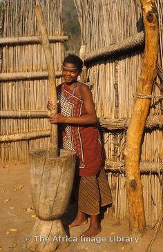 Swazi girl punding millet, Mantenga village, Swaziland