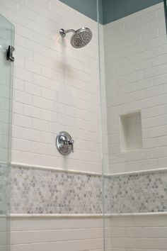 Beautiful shower is clad in white subway tiles accented with gray