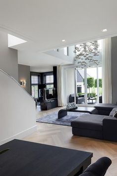 Gray white modern living room. Sectional Couch, modern pendant chandelier and gorgeous wood floors.