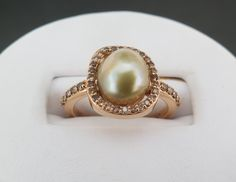 an 18k rose gold ring with 0.30 total carat weight round full cut cognac diamonds and an 8.5mm light golden-pistachio colored fresh water pearl.
