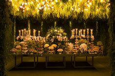 The dessert room is encased within walls of lush greenery ( like the center of a whimsical hedged labyrinth) and crowned with hanging gardens of greenery accented with lighting. Gorgeous! Gorgeous!