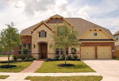 Mixing native stone with brick is a distinctive Texas touch. Design 6856 by Coventry Homes in the Southern Trails community. Pearland, TX.