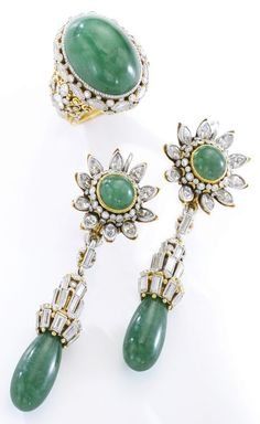 Emerald and diamond demi-parure, Elmar Seidler, first half of the 20th century. Comprising: a pair of earrings and a ring decorated on front and back with intricate metal work, millegrain-set with variously cut diamonds, drop-shaped and cabochon emeralds. Unsigned. #Seidler #retro #DemiParure #ring #earrings