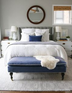 A white, navy, and gray bedroom perfect the neutral lover. Such a calming master bedroom retreat with gray painted walls.