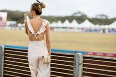 Curated by TRAVELLERS' ROBE www.travellersrobe.com - The best street style from the 2018 Alfa Romeo Portsea Polo. Here, a backless frilled jumpsuit with Yves Saint Laurent cream bag.