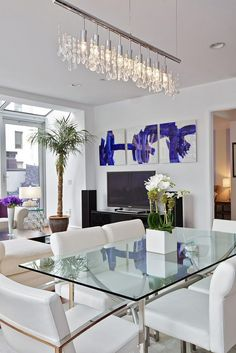 A glass table, simple leather white chairs and a horizontal crystal chandelier   | Usual House